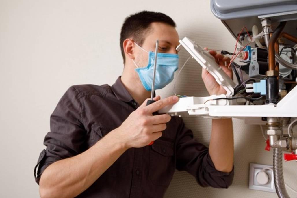 um-homem-consertando-uma-caldeira-com-uma-mascara-medica_93200-3347 (Setor de serviços como o de assistência técnica em residências teve aumento na procura em abril - Foto: Divulgação)